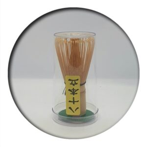 bamboo matcha whisk stood upright in packaging on white background
