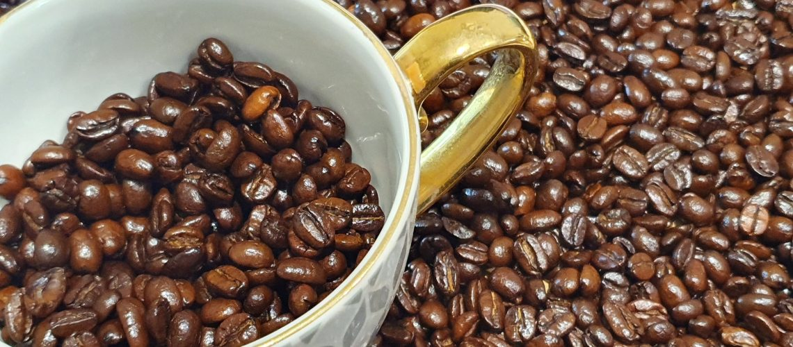 A cup of Arabica coffee beans surrounded by Coffee beans