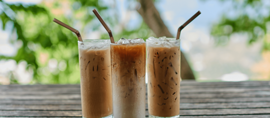 3 glasses of iced coffee with straws on a wooden table outside