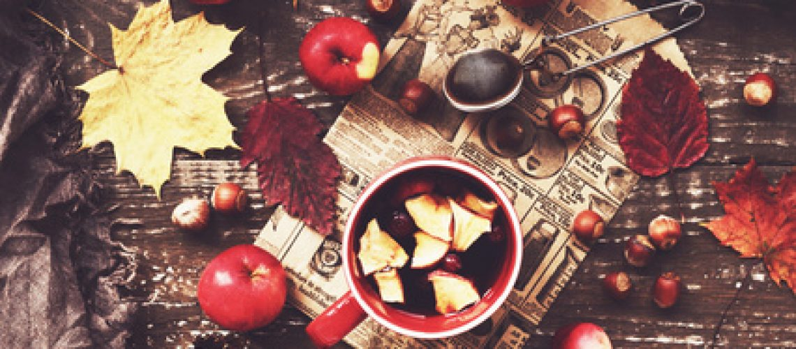 Cup of warming tea with apple and cranberry and woolen scarf, tabletop